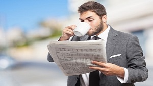 handsome young business man drinking and reading a newspaper